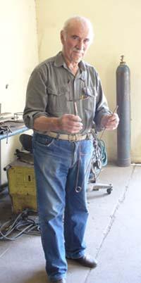 Pedro Belate muestra su varita de alambre de cobre, construida por él mismo.