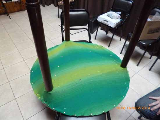 De izq. a der. Tela soporte de la espuma bajo el tablero de la mesa. Mesa impregnada de la espuma. Mesa en posición de trabajo. Ariel Farías se sentó próximo a la pata que tiene espuma.