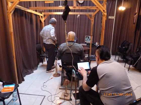 Imagen 6: Sujeto concentrado, de espaldas, tratando de levantar la pata de la mesa, con los electrodos fijados a su cabeza a través de un adminículo diseñado por Aníbal Melgar (en primer plano) y Andrea Romano especialmente para este caso.