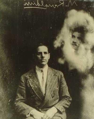 Fotograf&iacute;a trascendental obtenida en el C&iacute;rculo Crew, Inglaterra, el 8 de septiembre de 1928, por el Sr. M. Rinaldini. La nitidez de los rasgos y la abundancia de la sustancia flu&iacute;dica que la rodea muestran lo extraordinario del fen&oacute;meno que cobra toda su trascendental importancia cuando, en Buenos Aires, pudo identificar ese rostro, perteneciente a un ciudadano argentino fallecido hace 52 a&ntilde;os e identificado por sus sobrinos. [Fuente: <I>Album Primer Centenario del Moderno Espiritualismo (1848-1948).</I> Buenos Aires: Confederaci&oacute;n Espiritista Argentina (Fotograf&iacute;a-prueba indirecta)].