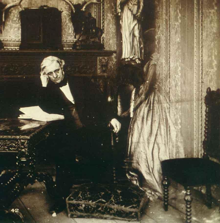 """""""La aparición de la difunta esposa a su desconsolado viudo"""" representa esta postal en un montaje fotográfico de fines del siglo XIX. Las experiencias de apariciones y encuentros pos-mortem en la viudez se recuerdan con frecuencia y pueden ser parte de una experiencia psicológica normal, no patológica."""